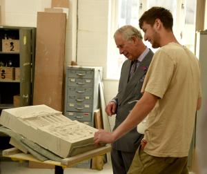 A stonemasonry student showing HRH The Prince of Wales his work during a Royal visit